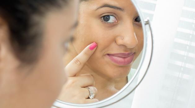 girl looking in the mirror and pointing at her face