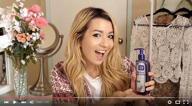 youtube star maybaby smiling with a clean and clear acne product in her hand