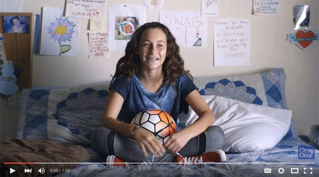 teenage girl sitting on a bed with a soccer ball