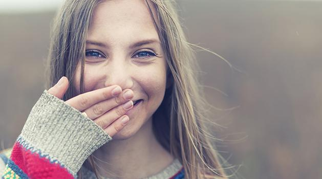 girl smiling with hand over her mouth