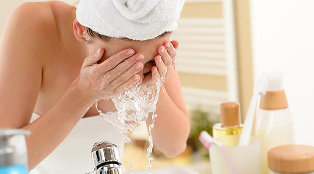 girl with a towel on her head washing face
