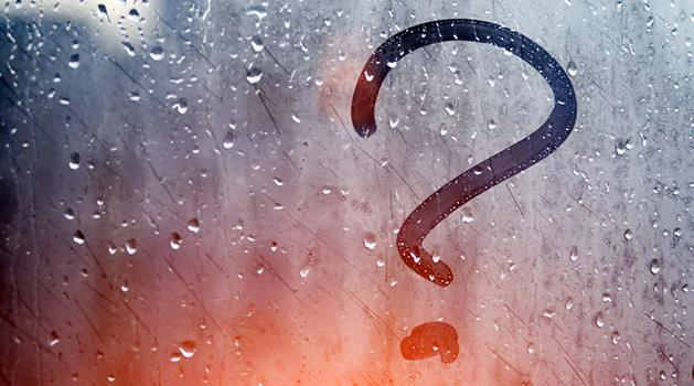 fogged window with rain drops and question mark